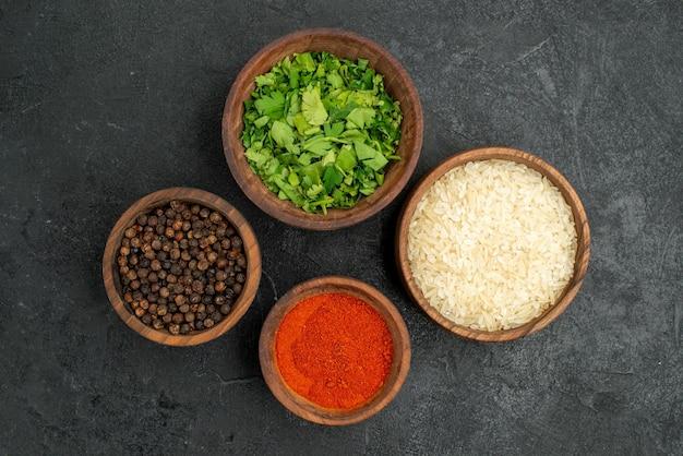 Верхний вид крупным планом специи в мисках, красочные специи, травы и рис на темной поверхности