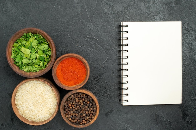 Top close-up view spices and notebook bowls of herbs black pepper rice and spices next to the white notebook on dark background