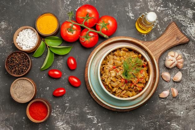 Vista ravvicinata dall'alto piatto di spezie di fagiolini aglio ciotole di spezie colorate foglie pomodori con pedicelli bottiglia di olio sul tavolo scuro