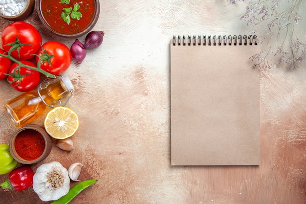 Top close-up view spices spices bottle of oil tomatoes lemon sauce cream notebook