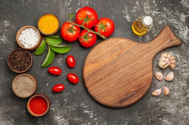 上部のクローズアップビュースパイスカラフルなスパイスのニンニクボウルの横にあるまな板は、暗いテーブルに小花柄のオイルのボトルとトマトを残します