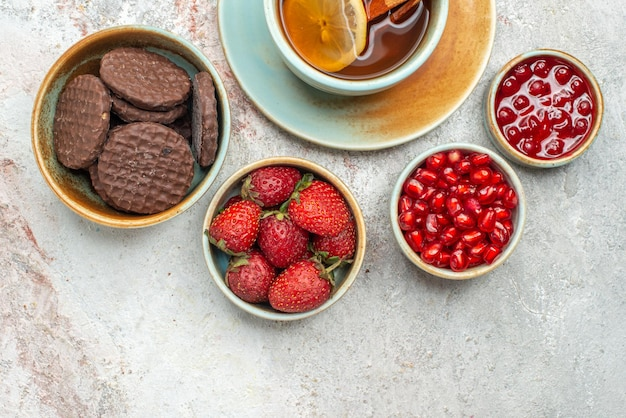 上のクローズアップビューイチゴテーブルの上のザクロのさまざまなベリーチョコレートクッキーシードのレモンとシナモンスティックボウルと紅茶のカップ