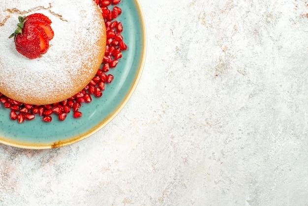Vista ravvicinata dall'alto torta di fragole piatto di torta con fragole e melograno sul tavolo luminoso