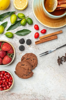 Top close-up view strawberries cookies berries in bowls cookies a cup of tea lime and lemon cinnamon sticks fork on the table