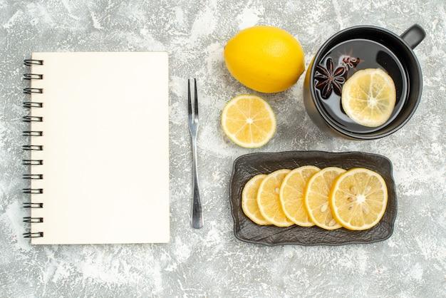 Сладости, вид сверху крупным планом, чашка чая с звездчатым анисом, лимонная вилка, блокнот