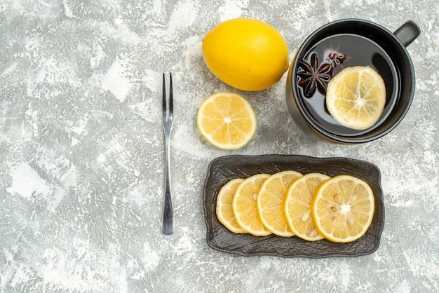 Сладости, вид сверху крупным планом, чашка чая с звездчатым анисом, лимонная вилка