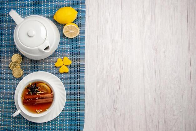 上のクローズアップビューお菓子とお茶一杯レモンとシナモンレモンティーポットとハーブティー一杯テーブルの左側にある市松模様のテーブルクロスにさまざまなお菓子