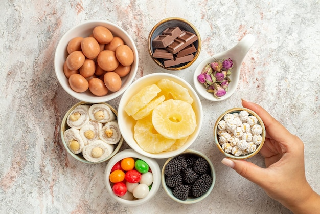 Top close-up view sweets in bowls the bowls of appetizing sweets dried fruits and berries in the hand