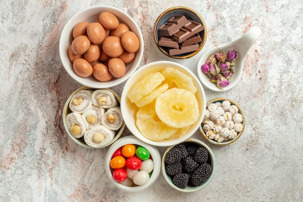 Top close-up view sweets in bowls eight bowls of different appetizing sweets and dried fruits and berries in the center of the white table