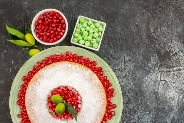 Vista ravvicinata dall'alto dolci una torta con agrumi ciotole di caramelle verdi e semi di melograno