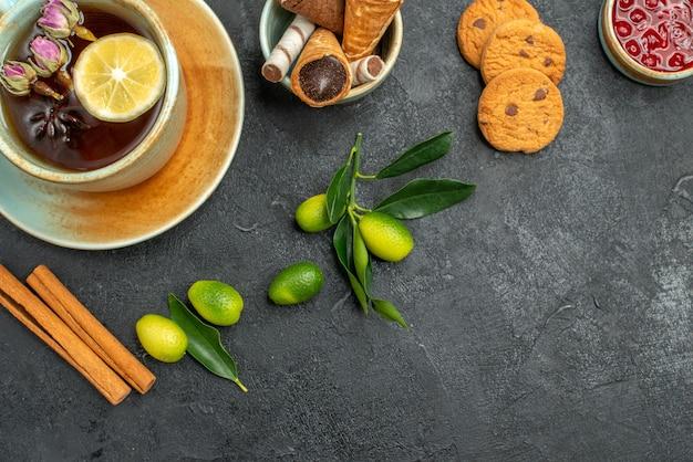 上のクローズアップビューお菓子クッキージャムはレモン柑橘系の果物とお茶のカップをワッフルします
