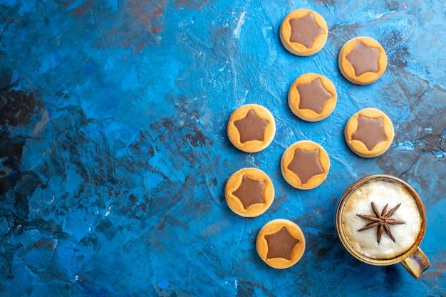 Vista ravvicinata dall'alto dolci una tazza di caffè accanto ai diversi biscotti