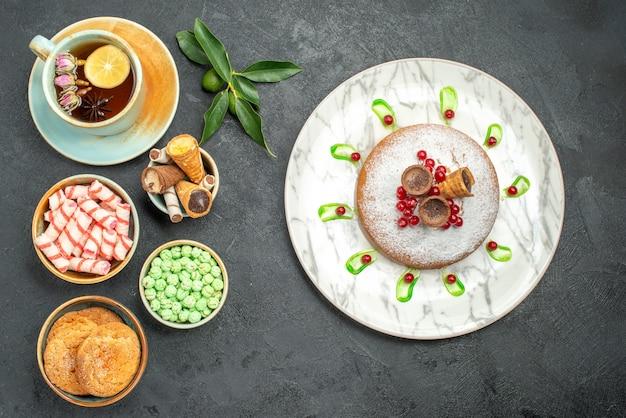 Top vista ravvicinata dolci una tazza di tè biscotti cialde caramelle agrumi torta con frutti di bosco