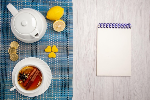 Top close-up view sweets and a cup of tea a cup of herbal tea with lemon and cinnamon lemon different sweets teapot on the checkered tablecloth next to the white notebook