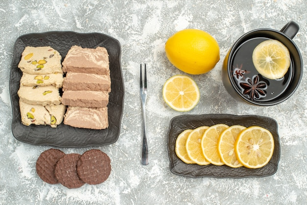 Top close-up view sweets a cup of tea lemon fork cookies sunflower seed halva