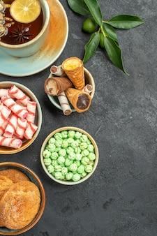Top vista ravvicinata dolci una tazza di tè cialde biscotti agrumi