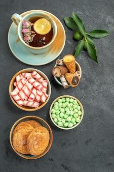 Top vista ravvicinata dolci una tazza di tè con biscotti al limone cialde dolci agrumi