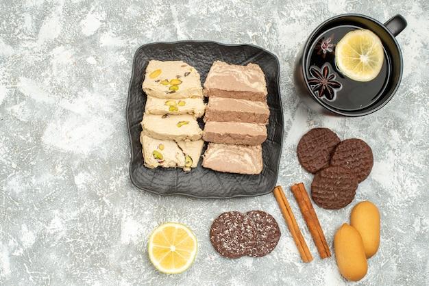 Vista ravvicinata dall'alto dolci una tazza di tè con biscotti halva al limone e semi di girasole