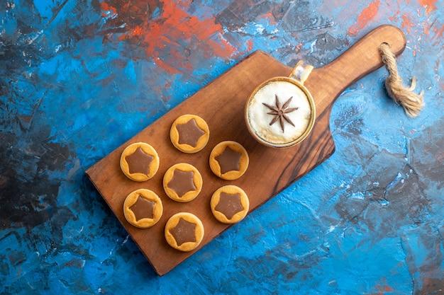 Вид сверху крупным планом сладости, разные виды печенья и чашку кофе на деревянной доске