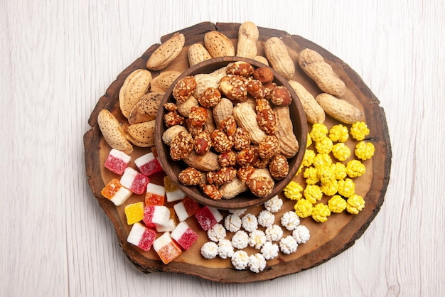 나무 판자에 있는 다채로운 사탕 옆에 있는 그릇에 있는 땅콩에 있는 상위 클로즈업 보기 과자