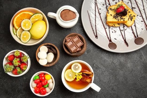 上部のクローズアップビューお菓子ボウルに柑橘系の果物のボウルチョコレートキャンディーイチゴチョコレートクリームケーキのプレートとお茶のカップ