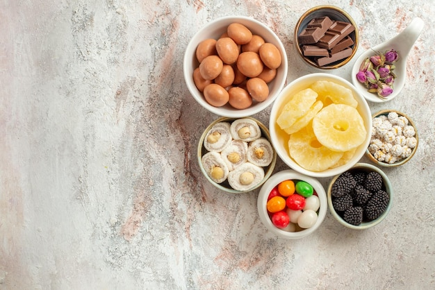 식탁에 있는 다양한 과자와 말린 과일, 딸기 8개 그릇에 있는 클로즈업 보기 과자