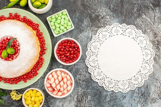 トップクローズアップビューお菓子レースドイリー柑橘系の果物とケーキのプレートライムカラフルなキャンディー