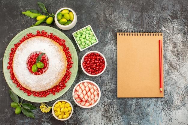 上部のクローズアップビューお菓子ノートブック鉛筆柑橘系の果物とケーキのプレートライムカラフルなキャンディー