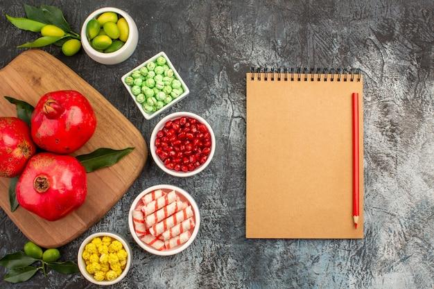 Vista ravvicinata dall'alto dolci taccuino matita caramelle colorate tre melograni sulla tavola della cucina