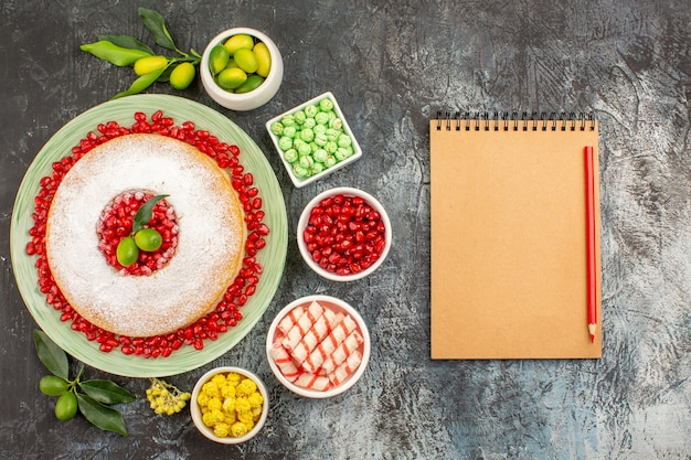 Top close-up view sweets notebook pencil a plate of cake with citrus fruits limes colorful candies