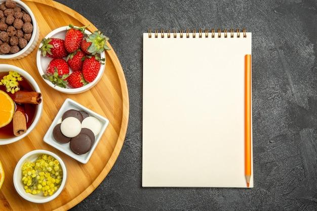 ヒゼルナッツのプレートの横に黄色の鉛筆が付いているテーブルノートの上のクローズアップビューのお菓子レモンチョコレートベリーレモンとシナモンスティックとお茶のカップ