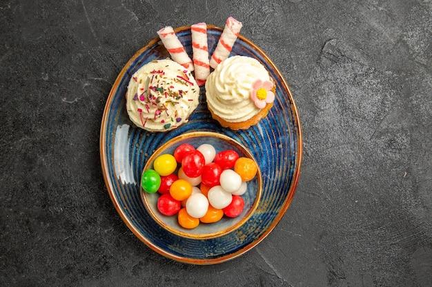 Сверху крупным планом вид сладостей на тарелке аппетитных кексов рядом с миской разноцветных конфет на темном столе