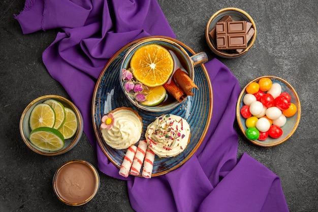 テーブルの上のクローズアップビューのお菓子レモンシナモンとお茶のカップは、柑橘系の果物とチョコレートクリームのカラフルなキャンディーチョコレートスライスのプレートボウルにクッキーを貼り付けます