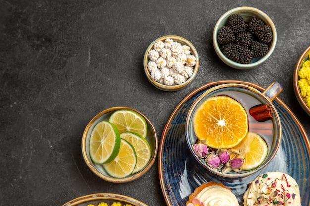 Сверху крупным планом сладости на столе, чаши со сладкими ягодами, цитрусовые, белые конфеты и кексы, и чашка чая с лимоном и корицей на темном столе