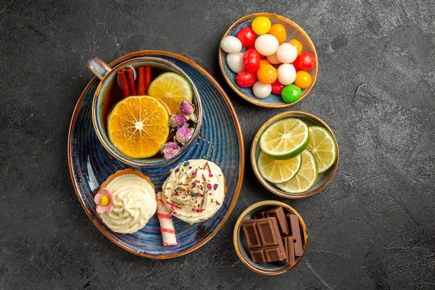 Сверху крупным планом вид сладостей на столе, тарелки аппетитных конфет, шоколада и ломтиков лайма рядом с синим блюдцем чашки черного травяного чая и двух кексов на столе