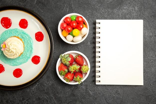カップケーキのプレートの横にあるテーブルの白いノートの上のクローズアップビューのお菓子と黒いテーブルの上のお菓子とイチゴのボウル