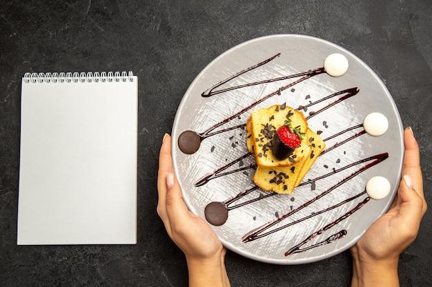 Vista ravvicinata dall'alto piatto di torta con fragole ricoperte di cioccolato e salsa di cioccolato nelle mani accanto al taccuino bianco