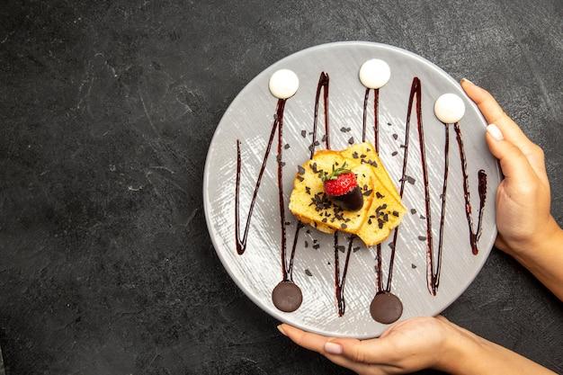 손에 초콜릿 소스와 초콜릿 덮인 딸기가 있는 케이크의 클로즈업 보기 과자 접시