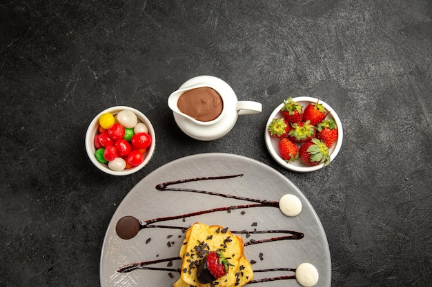 Vista ravvicinata dall'alto piatto di dolci di gustosi pezzi di torta con salsa al cioccolato e fragole accanto alle ciotole di caramelle fragole e salsa al cioccolato