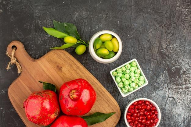 도마에 있는 상위 클로즈업 보기 과자 석류 녹색 과자 석류 감귤류 과일