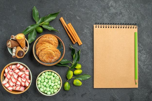 Вид сверху крупным планом сладости корица цитрусовые вафли печенье тетрадь карандаш