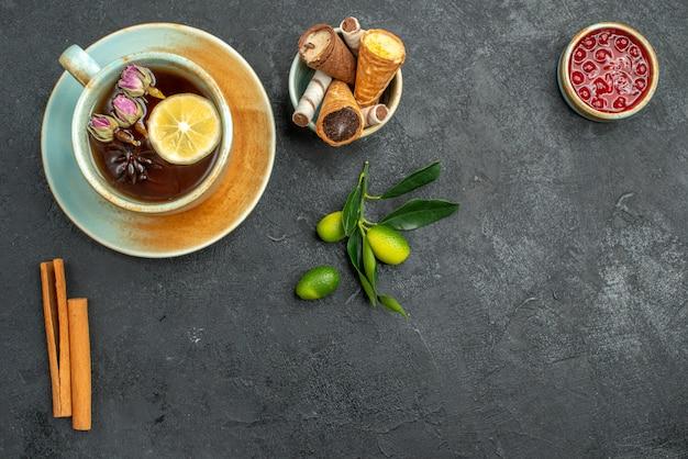 Top vista ravvicinata dolci cialde in una ciotola una tazza di tisane cannella bastoncini marmellata agrumi