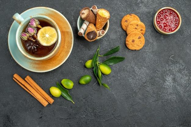 Top vista ravvicinata dolci cialde in una ciotola una tazza di tè biscotti cannella marmellata agrumi