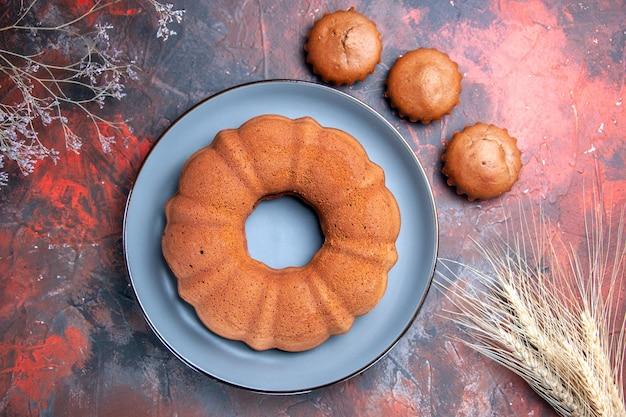 Vista ravvicinata dall'alto torta gustosa torta gustosa sul piatto blu tre cupcakes rami di albero