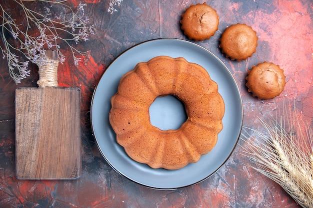 Вид сверху крупным планом вкусный торт, вкусный торт на синей тарелке, три кекса на разделочной доске