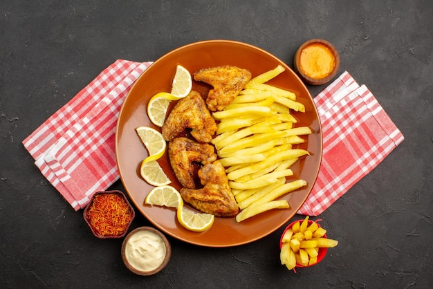 Top close-up view tasty chiken appetizing chicken wings french fries and lemon bowls of different types of sauces and spices on pink-white checkered tablecloth in the center of the dark table