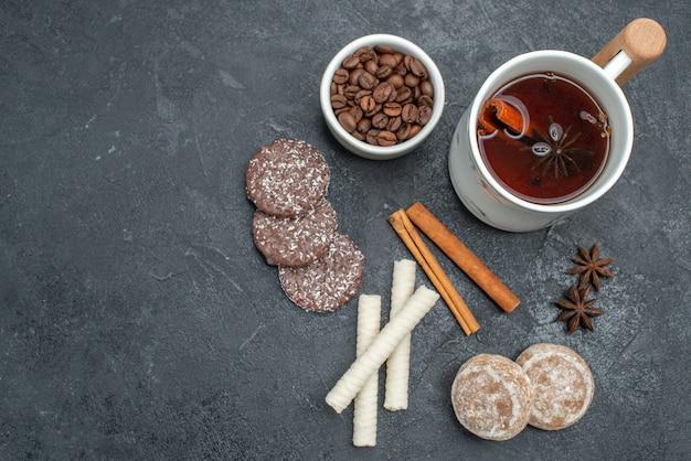 Top vista ravvicinata biscotti da tè una tazza di tè cannella anice stellato ciotola di chicchi di caffè