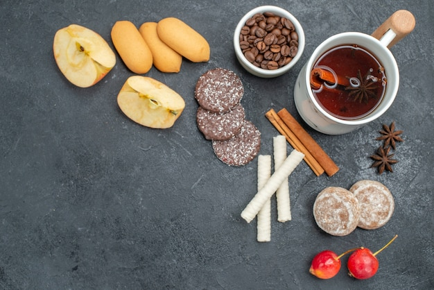 Top vista ravvicinata biscotti da tè una tazza di tè bastoncini di cannella anice stellato ciliegie chicchi di caffè
