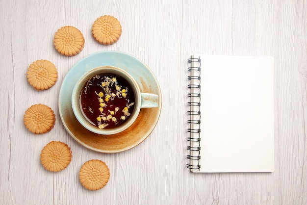 Top close-up view tea with cookies white cup of herbal tea next to the white notebook and cookies on the white table
