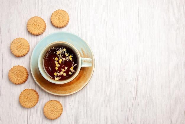 白いテーブルの上のクッキーの横にあるハーブティーの白いカップのクッキーとトップクローズアップビューティー